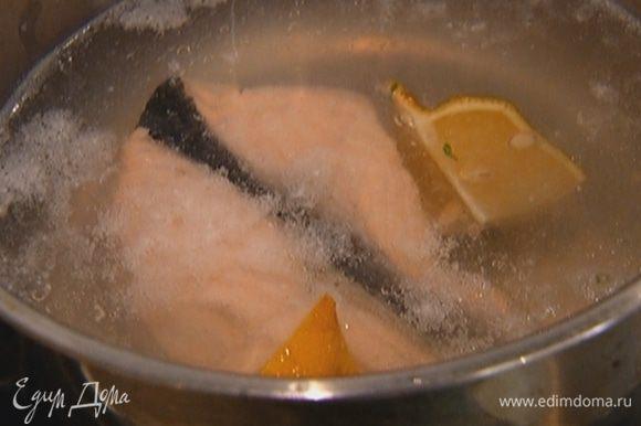 Стейк красной рыбы залить холодной водой, довести до кипения и варить 2 минуты. Выключить огонь, добавить в кастрюлю четвертинку лимона и, не сливая воду, дать рыбе остыть.
