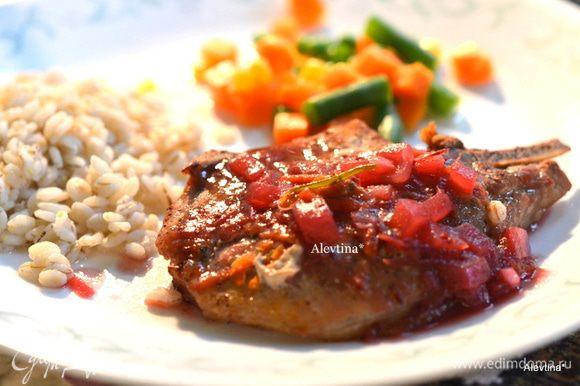 Готовые свиные отбивные подаем под клюквенным соусом с гарниром. Приятного аппетита.