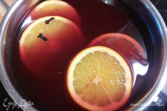 Ставим на огонь, добавляем нарезанный апельсин. Глинтвейн ни в коем случае нельзя доводить до кипения. При кипячении он моментально теряет свои вкусовые качества и большую долю содержания алкоголя. Как только пропала белая пена с поверхности вина, необходимо снять ёмкость с огня