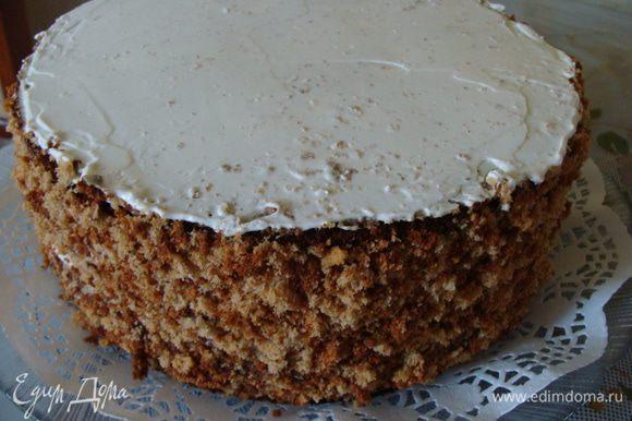 Далее уже стемнело, поэтому фото неяркие. Смазать верх торта оставшейся сметаной и посыпать бока торта бисквитной крошкой. Переложить торт на тарелку.