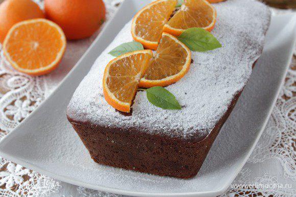 Готовому кексу дать остыть в форме 10-15 минут, затем аккуратно вынуть и остудить полностью. Посыпать сахарной пудрой, украсить дольками апельсина.