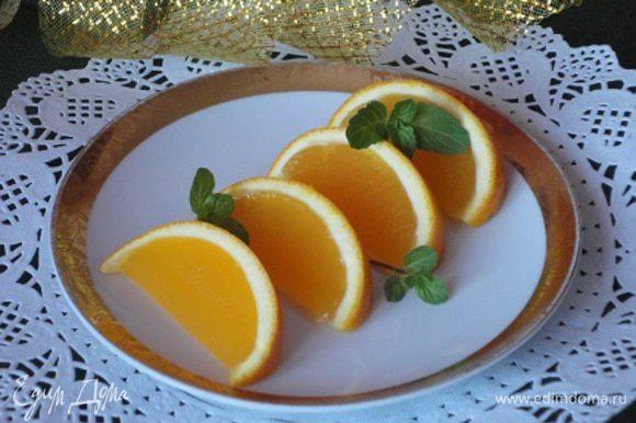 Аккуратно разрежьте фрукты с желе на дольки и подавайте на стол, украсив листочками мяты.