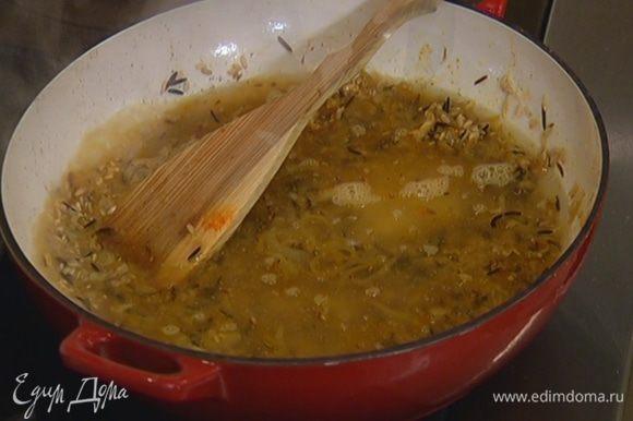 Всыпать рис, перемешать и дать ему пропитаться ароматами, затем влить горячий бульон, так чтобы рис был полностью покрыт.