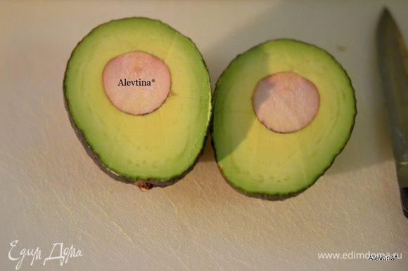 Листья салатные смесь выложим в емкость и смешаем, очистим авокадо от кожуры и ядра, разрежем на дольки.