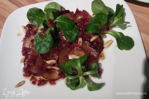 На сливу соус, выложите салат, не много, несколько веточек. И еще несколько капель соуса. Посыпьте кедровыми орешками.