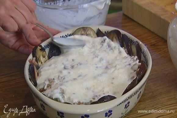 В жаропрочную керамическую форму выложить в один слой обжаренные полоски баклажанов, так чтобы получились бортики, затем разложить мясной фарш и равномерно залить его сырным соусом.