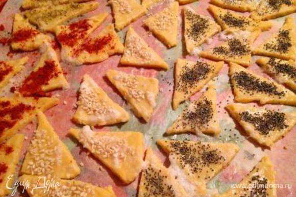 Затем разделить шар пополам и каждую часть раскатать на пергаментном листе в квадрат 20х20 см, разрезать на 16 квадратов и каждый перерезать по диагонали, чтобы получились треугольники. Смазать треугольники взбитым белком и присыпать маком, кунжутом, орегано, сладкой паприкой, розмарином, а можно и просто солью на ваше усмотрение. Мне больше всего нравятся треугольники с маком и кунжутом.