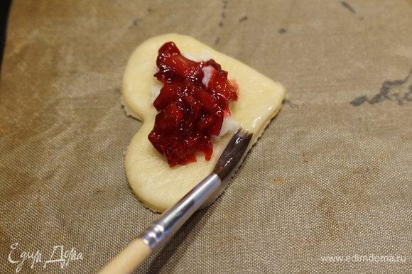 На противень, застеленный пергаментом выложить заготовки теста-сердечки, сверху выложить сливочный сыр и вишневую начинку. Белок слегка взбить с молоком. Маленькой кисточкой смазать им края пирожков. Лучше смазывать по 2-3 пирожка за один раз, чтобы белок не подсыхал и тесто потом лучше склеилось.