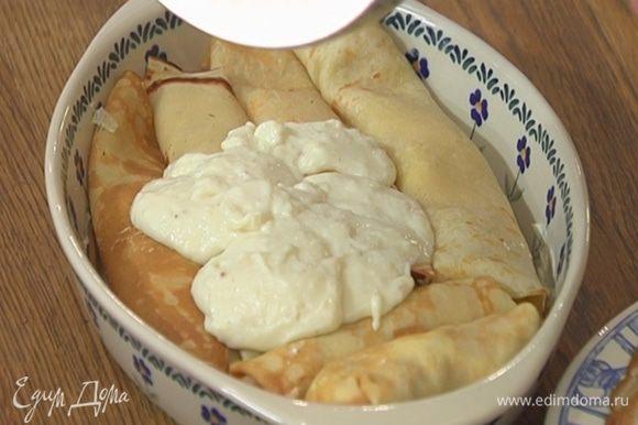 Жаропрочную керамическую форму смазать оставшимся сливочным маслом, выложить свернутые блины и залить соусом бешамель.
