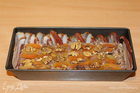 Бекон выложить на дно, курагу разрезать на 2-3 части. Орехи поломать на небольшие кусочки (или вообще не ломать). В форму положить половину фарша. Сверху орехи и сухофрукты.
