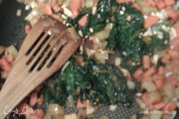 Затем выложить на разогретое в сковородке растительное масло, поджарить до прозрачности лука, выложить мороженый шпинат, продолжать жарить,
