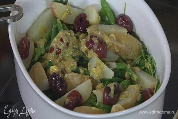 Руколу выложить в глубокую тарелку, полить частью заправки, сверху разложить фасоль, картофель, оливки и полить оставшейся заправкой.