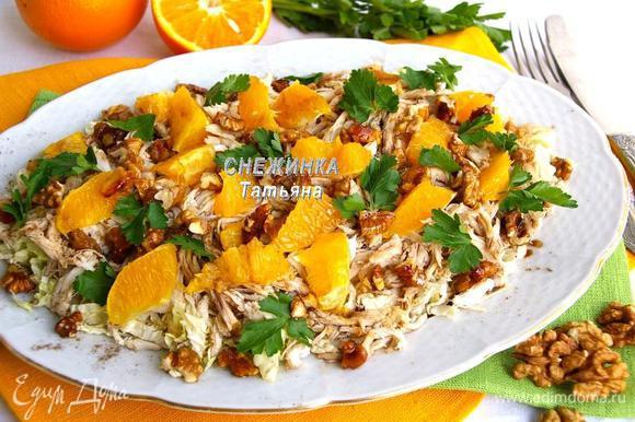 Остывшие орехи ломаем руками на кусочки и выкладываем сверху. Украшаем салат листиками петрушки и молотым перцем.