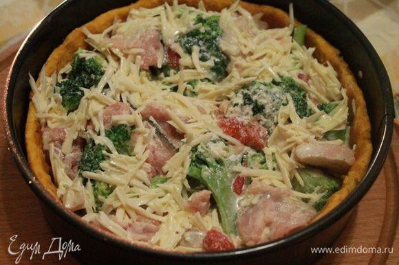 Достать тесто, убрать груз и выложить рыбу и капусту вперемешку. Вылить заливку, равномерно распределяя сыр по начинке.