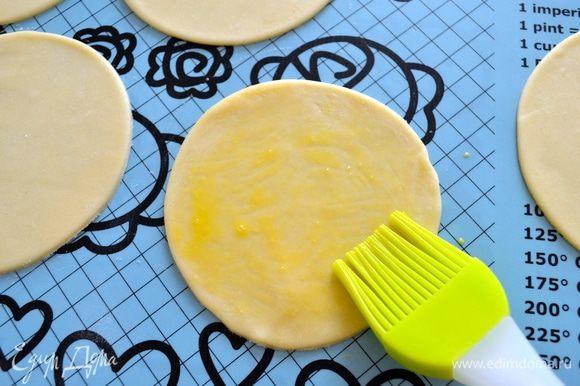 Яйцо слегка взбить в чашке (мисочке). Смазать первый диск из теста яйцом.