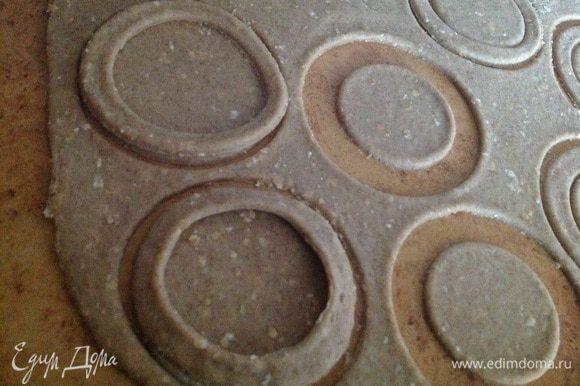 Тесто раскатать примерно 3-4 мм. Вырезать формой круги, а в половине кругов сделать середину меньшего диаметра - получатся ободки. Выложить вырезанные ободки на круг, и хорошо прижать края!