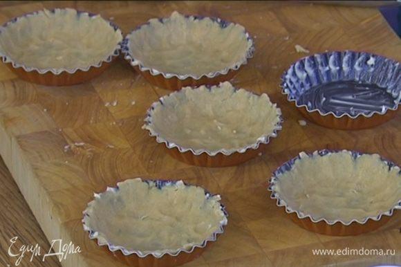 Небольшие формы для выпечки смазать оставшимся сливочным маслом и равномерно распределить тесто по дну и стенкам, сформировав бортики. Часто наколоть тесто вилкой и отправить в морозильник.