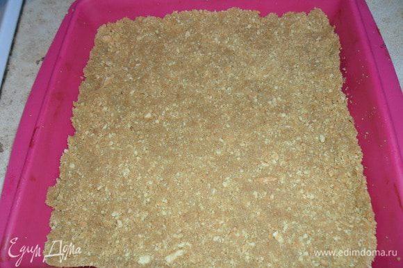 В крошку влить растопленное сливочное масло и выложить в форму, хорошо утрамбовать. Отправить в холодильник.