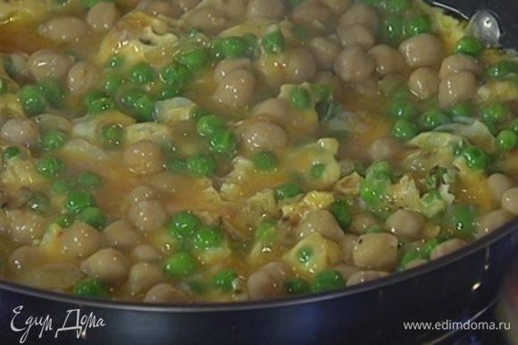 В сковороду с горохом влить яичную массу. Когда края омлета схватятся, накрыть его крышкой.
