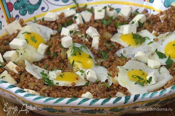 Сверху на гречку с сыром выложить перепелиные яйца и посыпать оставшимся сыром и зеленью.
