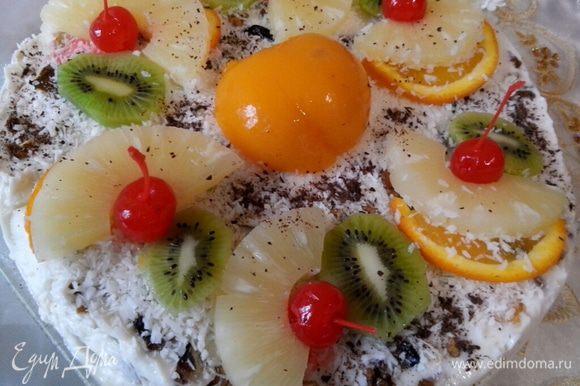 Украшаем торт. Посыпаем кокосовой стружкой, выкладываем фрукты и слегка посыпаем тертым шоколадом.