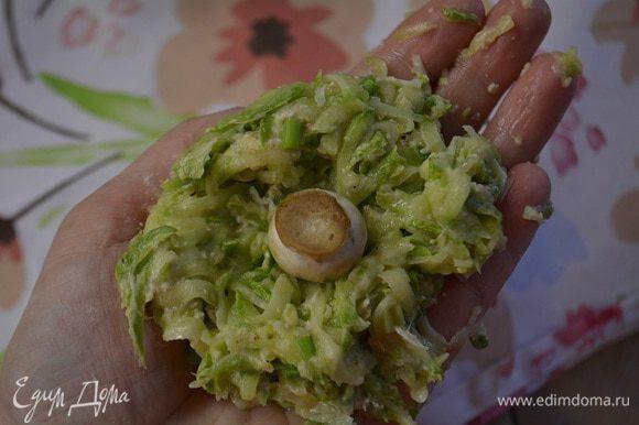 Влажными руками сформировать лепешку, на середину положить гриб и сформировать шарик.
