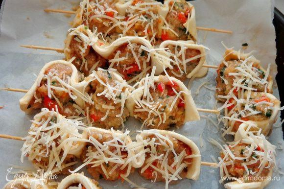 На деревянные шпажки наколоть тесто и слепленные мясные шарики. При желании посыпать их тертым сыром. Запекать в духовке при 200 градусах около 45 минут.
