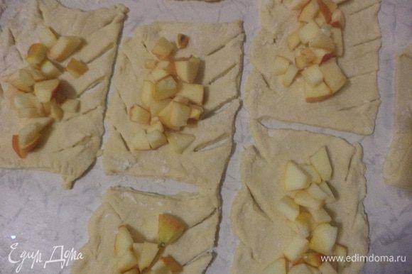 В центр каждого прямоугольника выложить яблоки, посыпать сахаром. По краям теста с двух сторон сделать диагональные надрезы.