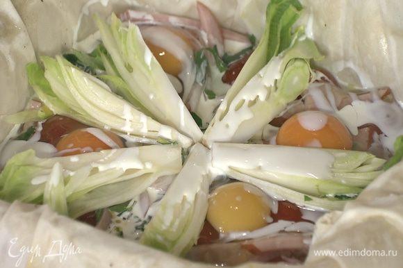 Подпеченное тесто с помидорами вынуть из духовки, выложить в форму ветчину, посыпать половиной зелени, разбить сверху яйца и полить все половиной сливок, затем выложить цикорий и сбрызнуть оставшимися сливками.