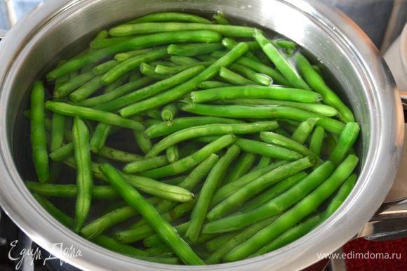 """Первым делом подготовить овощи, которые должны пройти термическую обработку. Зеленую стручковую фасоль вымыть и обрезать """"хвостики"""" по краям. Выложить подготовленные таким образом стручки фасоли в кипящую воду. Проварить 3-4 минуты."""