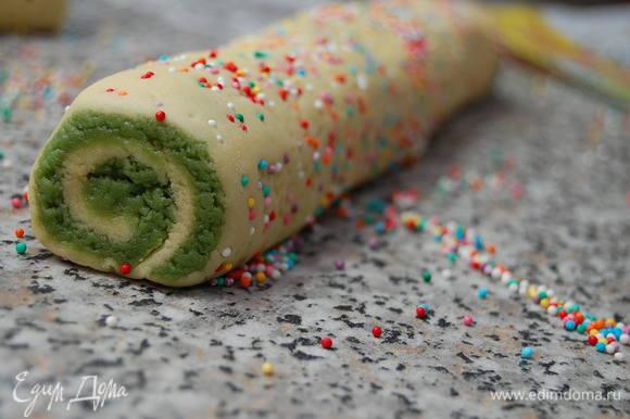 Раскатать обе части теста по отдельности между двумя листами бумаги для выпечки. Если тесто будет слишком мягким - уберите его на несколько минут морозилку. Далее поверх светлой части теста выложить зеленое и скрутить плотным рулетом. Обвалять рулет в кондитерской посыпке, прикрыть пищевой пленкой и убрать в холодильник на 1 час.