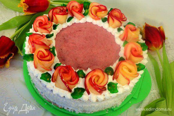 Бока торта смазать взбитыми сливками и обсыпать кокосовой стружкой. Края бисквита декорировать при помощи кулинарного шприца взбитыми сливками и украсить розами из яблок. Листики из порезанного пластинками зеленого кумквата.
