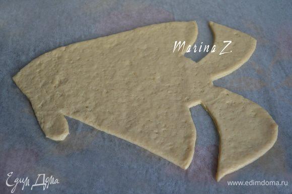 Удобнее всего раскатанное тесто сразу переложить на пергамент и на нем вырезать заготовку. Лишнее тесто убрать.