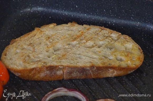 Хлеб обжарить с двух сторон на сковороде-гриль, где жарилась колбаса с луком и помидорами.
