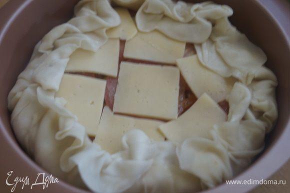 Оставшийся помидор режем тонкими кружочками и выкладываем поверх начинки. Сыр режем тонкими пластинами и также выкладываем на начинку. Собираем свисающие края теста, формируя бортик.