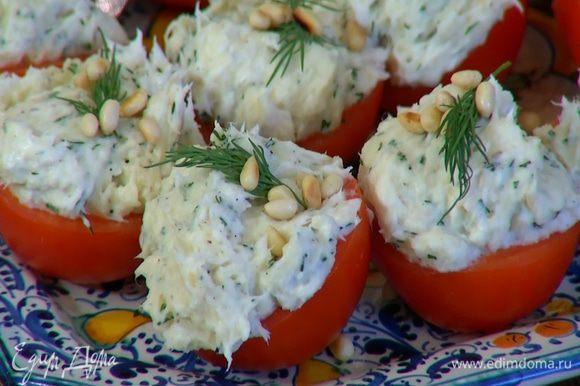 В чашечки помидоров выложить картофельно-рыбное пюре, посыпать орехами и украсить оставшимся укропом.