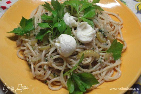 Спагетти отварить до состояния аль-денте. Соединить с сельдереем, песто и перемешать. Пасту подавать с зеленью и сыром моцарелла.