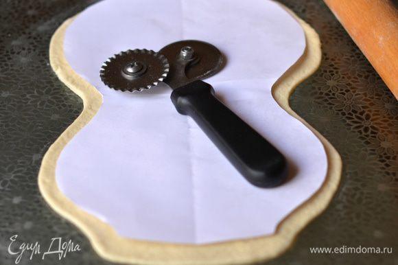 Раскатать 2 часть теста в овал. Приложить шаблон и вырезать, отступая от контура на 1,5-2 см.