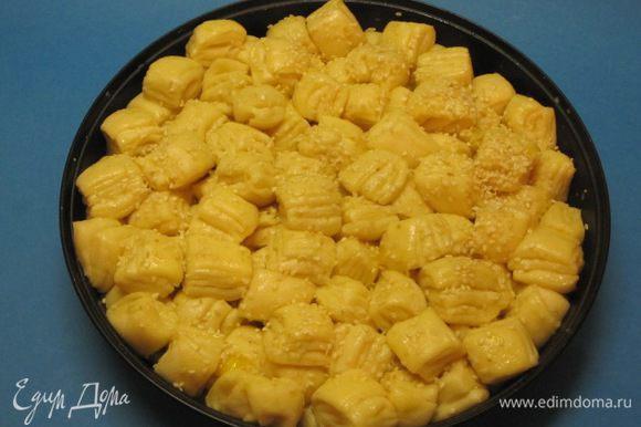 Накрыть форму пищевой пленкой и оставить на 30 минут. Желток слегка взбить с 10 мл молока, аккуратно смазать верх пирога. Сверху посыпать кунжутом.