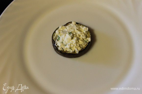Приступим к сборке: на кружок баклажана кладем сыр с зеленью.