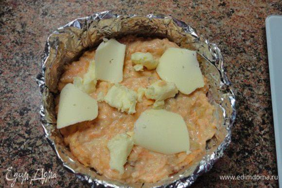 Формочки смазать маслом, посыпать сухарями, выложить морковную массу, а сверху кусочки сливочного масла.