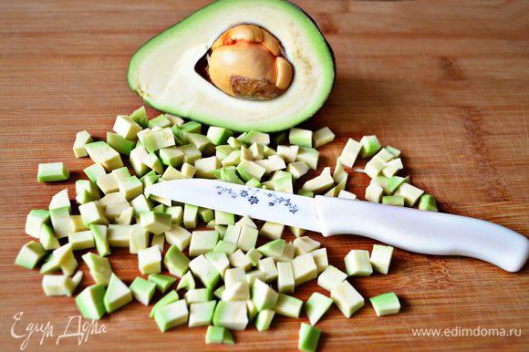 Авокадо разрезать пополам, вынуть косточку, удалить с авокадо шкурку, мякоть нарезать кубиками, сбрызнуть лимонным соком.