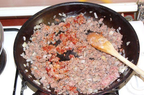 Лук мелко режем и обжариваем на масле в сковороде. Добавляем фарш и обжариваем еще пару минут. Потом наступает очередь томатной пасты, ее тоже надо обжарить вместе с фаршем.