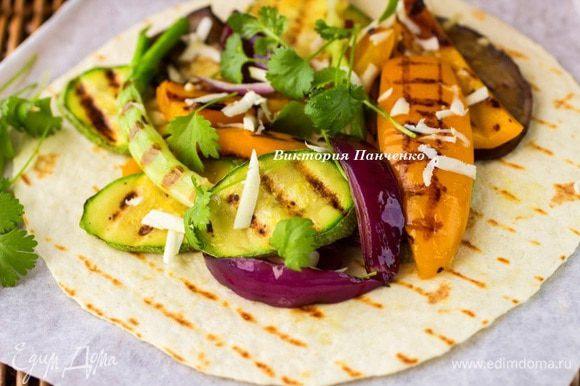 На каждую выложить горку овощей, посыпать брынзой, натертой на крупной терке, добавить веточки кинзы и базилика.