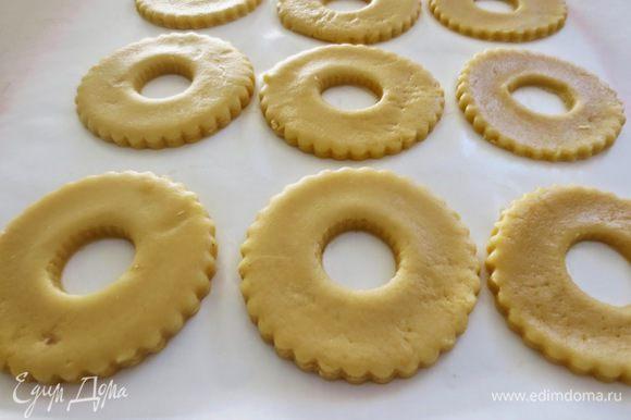Рабочую поверхность присыпать мукой, из теста раскатать пласт толщиной примерно 8 мм. При помощи круглых формочек вырезать кольца. В центре каждого кольца, вырезать отверстие диаметром 2 см. Противень застелить пекарной бумагой и положить кольца, оставляя расстояние между ними. Противень положить в холодильник на 20 минут.