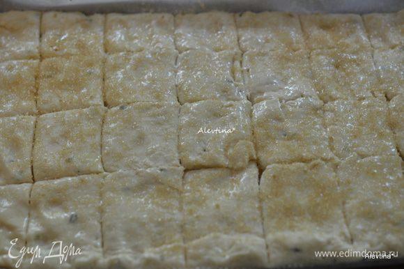 Разрезать или обозначить на небольшие квадратики, так чтобы нож не доходил до конца, смазать белком. Посыпать крупным сахаром. Поставить в горячую духовку на 25 мин.