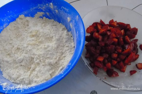 Смешать муку с маслом в крошку, добавить разрыхлитель и сахар. Клубнику почистить и нарезать.