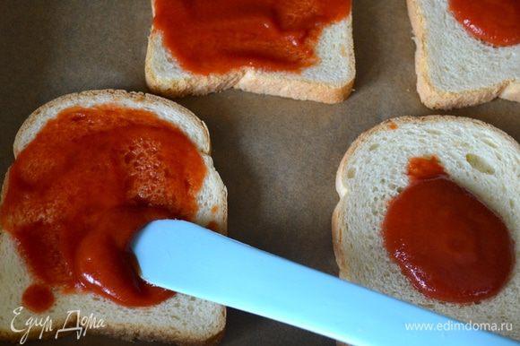 Духовку включить на 200 градусов. На противень застеленный пекарской бумагой выложите ломтики хлеба. Смажьте его томатным соусом (пассата).