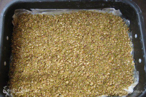 Форму смазать сливочным маслом, выложить первый лист фило, смазать маслом, выложить 3 слоя фило, каждый смазывать маслом. Выложить половину орехов, разровнять.
