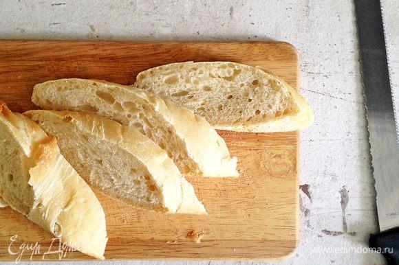 Чиабатту или багет нарезаем по диагонали. Кусочки не должны быть очень тонкими - около 2-2,5 см (тогда снаружи они будут хрустящие, а внутри мягкие).